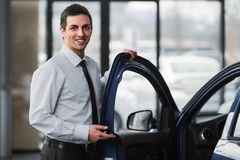 Car sales. Young smiling man in showroom is standing near car royalty free stock photo