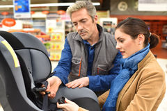 Car salesman advising client at the store. Car shop seller helping customer to choose child seat Royalty Free Stock Photos