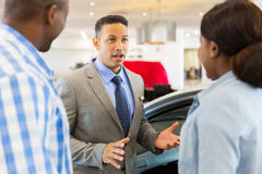 Car salesman african couple. Middle aged car salesman talking to african couple inside showroom stock photos