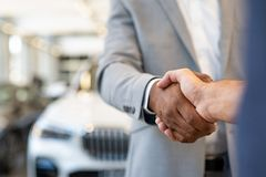 Car salesman and client handshake. Closeup of a salesman shaking hands with his client after selling him a car at the dealership. Handshake between customer and stock photography