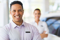 Car salesman colleague. Car salesman standing in front of colleague in showroom Royalty Free Stock Photos