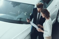Car Salesman Consultant Showing Contract to Woman. Beautiful Young Woman Talking to Caucasian Handsome Bearded Car Dealership Worker while Choosing Luxury royalty free stock images