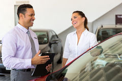 Car salesman customer. Middle aged car salesman talking to a customer in showroom stock photography