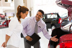 Car salesman customer. Middle aged car salesman talking to a customer in showroom Royalty Free Stock Photos