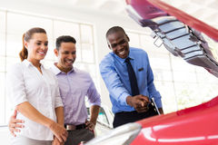 Car salesman engine. Happy african car salesman showing car engine to customers stock photo