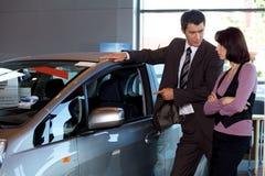 Car salesman explaining car features to customer Royalty Free Stock Photography