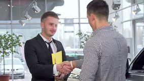 Car salesman giving car keys to the customer after shaking hands. Professional cars dealer selling automobile to client, sealing the deal with handshake royalty free stock photography