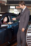 Car salesman giving the car keys to a young woman royalty free stock photos
