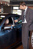 Car salesman giving the car keys to a young woman Royalty Free Stock Photo