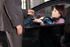 Car salesman giving the car keys to a young woman royalty free stock photography
