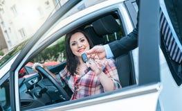 Car salesman giving car keys to young woman. Car salesman giving car keys to pretty young woman stock photography