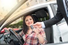 Car salesman giving car keys to young woman, light effect. Car salesman giving car keys to pretty young woman, light effect royalty free stock photo