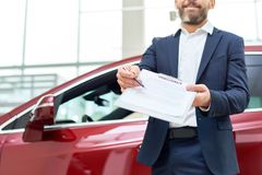 Car Salesman Giving Contract to Client. Mid section portrait of smiling bearded salesman handing purchase contract to client buying brand new car in luxury Stock Photo