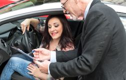 Car salesman giving explanations on clipboard to young woman. Car salesman giving explanations on clipboard to pretty young woman royalty free stock image
