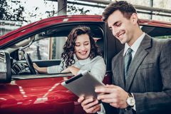 Car salesman giving explanations on tablet to pretty young woman. Close up view royalty free stock photos