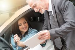 Car salesman giving informations on tablet to young woman, light effect. Car salesman giving informations on tablet to young women outdoors, light effect Royalty Free Stock Image
