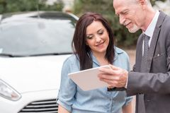 Car salesman giving informations on tablet to young woman. Car salesman giving informations on tablet to young women outdoors Stock Photography