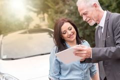 Car salesman giving informations on tablet to young woman, light effect. Car salesman giving informations on tablet to young women outdoors, light effect Royalty Free Stock Photos