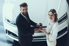 Car Salesman Giving Key of New Auto to Owner. Young Attractive Successful Buisness Woman Shaking Hands after Finishing Up Meeting about Buying White Luxury Car stock images