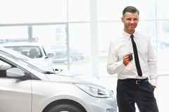 Car Salesman Giving Key of New Car at Showroom.  stock photography