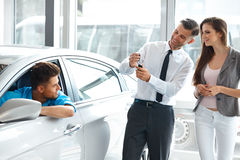 Car Salesman Giving a Key From the New Car to the Young Owners Royalty Free Stock Photos