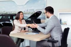 Car salesman giving the key of the new car to the young attractive girl. Young Car salesman giving the key of the new car to the young attractive girl royalty free stock photo