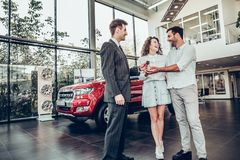 Its good choice!Car salesman is giving the key of the new car to the young attractive owners royalty free stock image