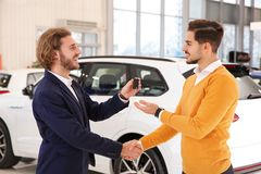 Car salesman giving key to customer while shaking hands. In dealership stock photos