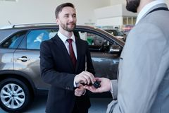 Car Salesman Giving Keys to Client. Waist up portrait of smiling handsome car salesman giving car keys to client standing in showroom of luxury dealership stock photos
