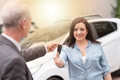 Car salesman handing car keys to young woman, light effect. Car salesman handing car keys to young women outdoors, light effect Royalty Free Stock Photo