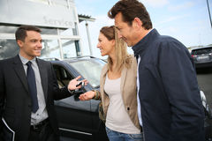 Car salesman handing keys to clients. Salesman in car dealership giving keys to clients stock image
