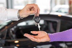 Car salesman handing over car keys in dealership Stock Photos