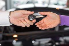 Car salesman handing over car keys in dealership Stock Images