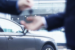 Car salesman handing over the keys for a new car to a young businessman, close-up Royalty Free Stock Photo