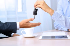 Car salesman handing over the keys for a new car to a young businessman. Focus on a key Royalty Free Stock Photos