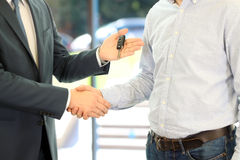Car salesman handing over the keys for a new car to a young businessman. Handshake between two business people. Focus on a key Royalty Free Stock Photos