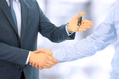 Car salesman handing over the keys for a new car to a young businessman . Handshake between two business people. Focus on a key.  Stock Photo