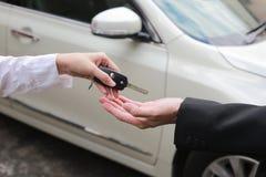Car salesman handing over the keys for a new car to young businessman. Car salesman handing over the keys for a new car to young businessman stock photos