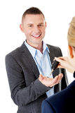 Car salesman handing over the keys. For a new car to a young businessman Royalty Free Stock Images