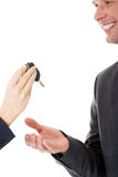 Car salesman handing over the keys. For a new car to a young businessman Royalty Free Stock Photos