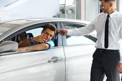 Car Salesman Handing over new Car Key to Customer at Showroom Stock Photos
