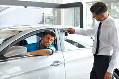 Car Salesman Handing over new Car Key to Customer at Showroom.  Stock Photo