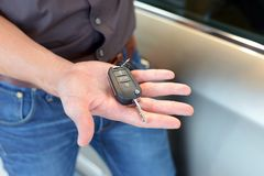 car salesman hands over the car key in the car dealership to customers royalty free stock photography