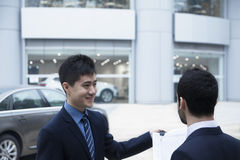 Car salesman holding car keys and paperwork and selling a car to a young businessman Royalty Free Stock Photos