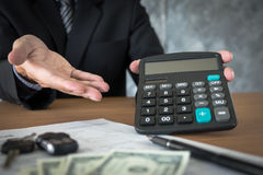 Car salesman holding a key and calculating a price at the dealer Stock Photography