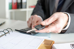 Car salesman holding a key and calculating a price Royalty Free Stock Photos