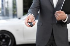 Car salesman holding key and presenting new auto. At show outdoors stock images