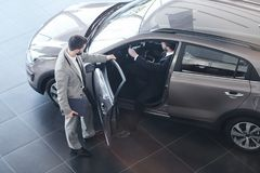 Car Salesman Opening Door to Client. Full length high angle view at bearded car salesman opening door for customer getting into his brand new luxury car, copy stock photos