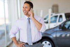 Car salesman phone. Handsome car salesman talking on cell phone in showroom stock photos
