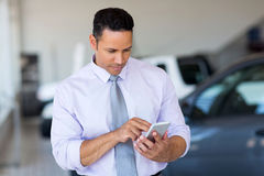 Car salesman phone. Mid age car salesman using cell phone in showroom stock photo